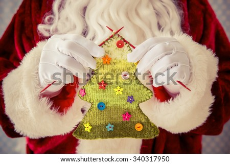 Santa Claus holding knitted Christmas tree in hands - stock photo