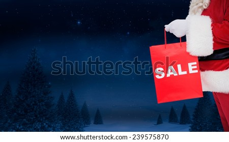 Santa claus holding sale bag against night sky over forest - stock photo