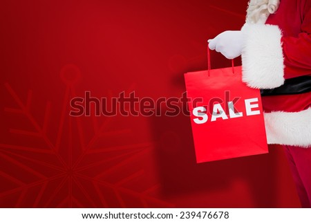 Santa claus holding sale bag against red snowflake background - stock photo