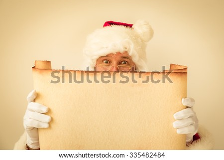 Santa Claus holding scroll paper blank. Christmas holiday concept - stock photo