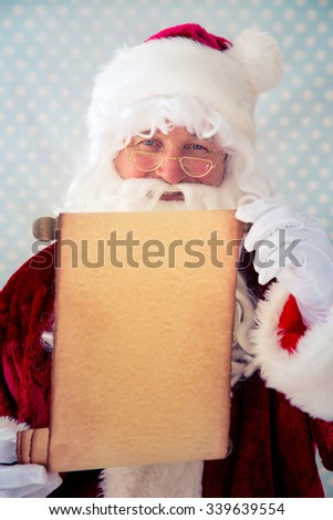 Santa Claus holding scroll paper blank in hands. Christmas holiday concept - stock photo