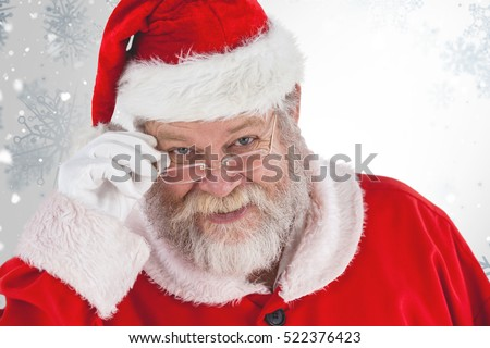 Santa Claus holding spectacles against snowflake pattern