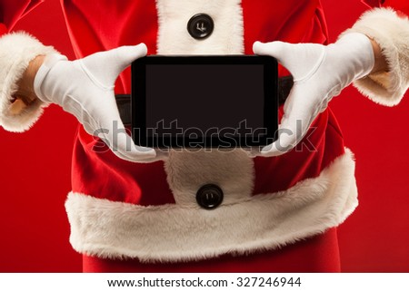 Santa Claus holding tablet, red background, hands