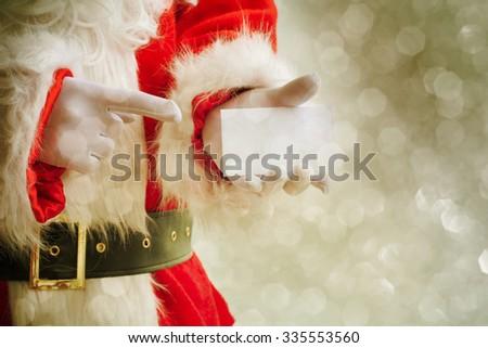 Santa Claus holding visit card - stock photo