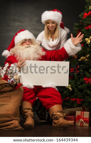 Santa Claus holding white blank sign with his wife and helper - stock photo