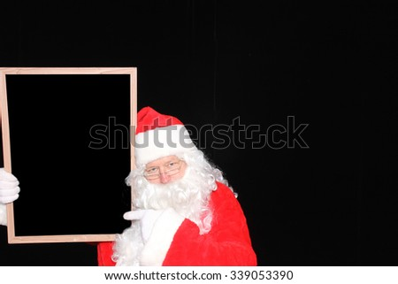 Santa Claus holds a Blank White Sign with room for your text or advertising or message. Santa Claus advertises your product or service with his blank sign while isolated on black velvet. - stock photo