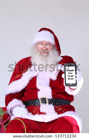 Santa Claus holds a cell phone with a blank white screen.