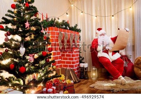 Santa Claus in a Christmas list with a gift in the hands of the fireplace and Christmas tree.