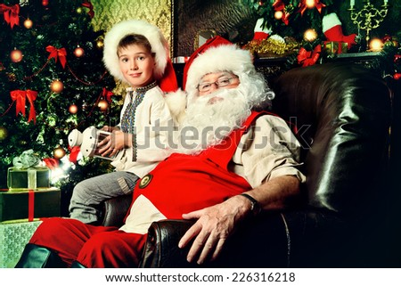 Santa Claus in his everyday clothes in Christmas home decor. Happy little boy helps Santa Claus get ready for Christmas. - stock photo