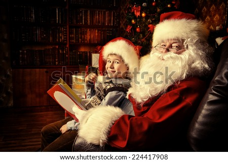 Santa Claus in his everyday clothes in Christmas home decoration. Happy little boy helps Santa Claus get ready for Christmas. - stock photo