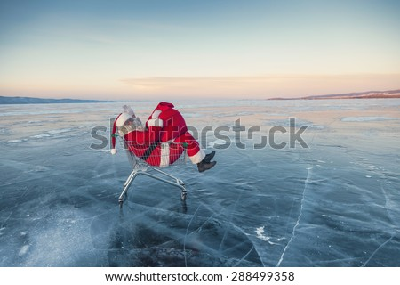 Santa Claus in the truck with a bag of gifts on winter lake ice - stock photo
