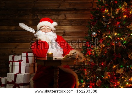 Santa Claus  in wooden home interior with letters and quill pen in hands