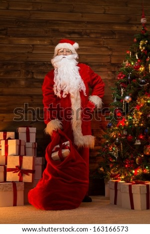 Santa Claus in wooden home interior with sack full of Christmas presents