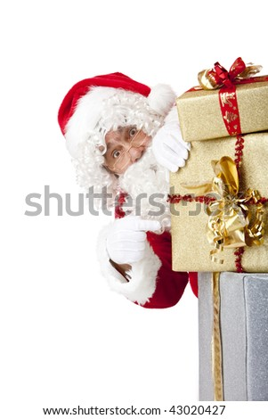 Santa  Claus is hiding behind a stack of Christmas gift boxes and points on them. Isolated on white.