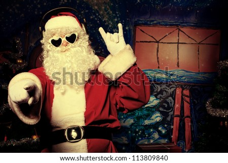 Santa Claus is listening to music in headphones. Christmas. - stock photo