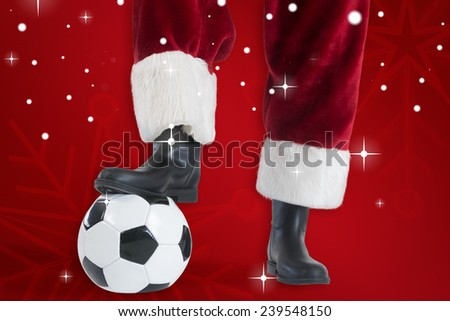 Santa Claus is playing soccer against red snowflake background - stock photo