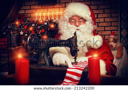 Santa Claus is sewing on a sewing machine striped socks for Christmas. - stock photo
