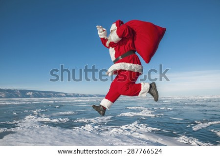 Santa Claus jumps over the frozen lake - stock photo