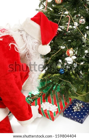 Santa Claus leaving gifts under the Christmas tree.   - stock photo