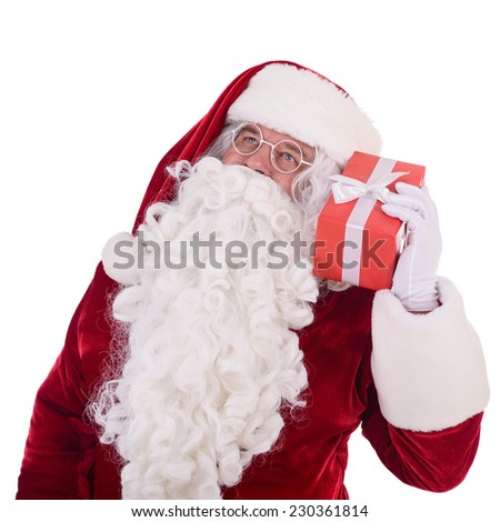 Santa Claus listen to gift box. Isolated on white background - stock photo