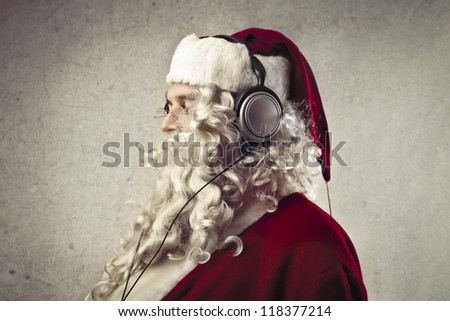 Santa Claus listening to the music with a pair of headphones - stock photo