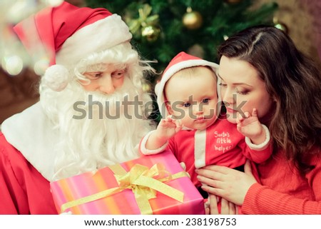 Santa Claus. little boy and his mother  holding gifts near  Christmas tree