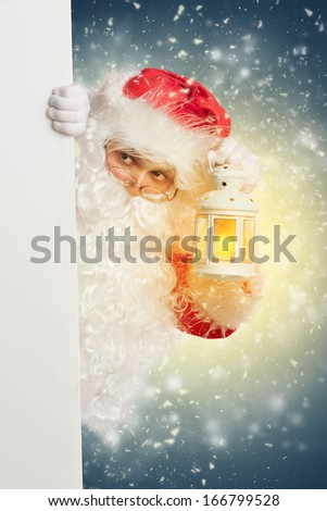 Santa Claus looking from behind white blank banner holding a shining lantern - stock photo