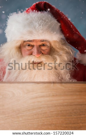 Santa Claus looking into wooden box outdoors. Light is coming from inside to his face. Opening Christmas magic concept. - stock photo