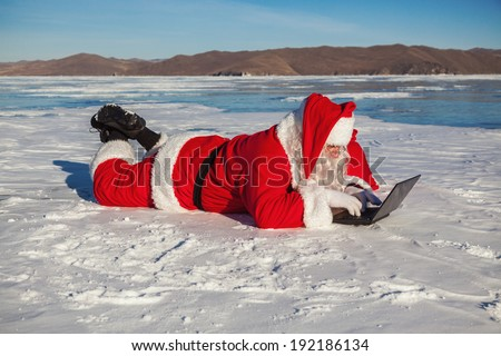 Santa Claus lying on the snow , looking at laptop news, shooting was conducted in a sunny day on lake Baikal - stock photo