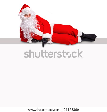 Santa Claus lying on top of a blank billboard sign pointing at an empty white area where you can add your own text. - stock photo