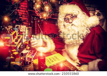 Santa Claus making Christmas gifts at home. - stock photo