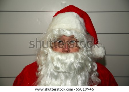 Santa Claus Mugshot. Santa is scared as his mugshot is taken for his arrest photo - stock photo