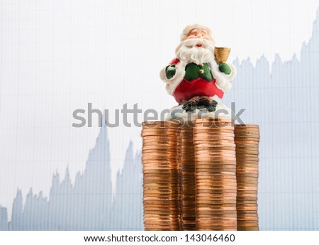 Santa Claus on a stack of coins with financial report background - stock photo