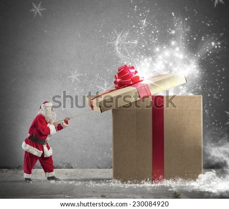 Santa Claus opening a big red gift - stock photo