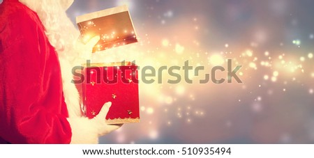 Santa Claus opening a red Christmas present on shiny light background