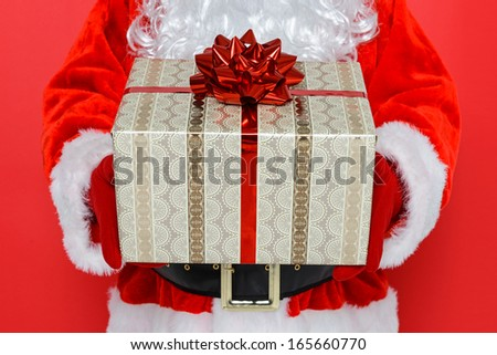 Santa Claus or Father Christmas giving you a gift wrapped present, red background.