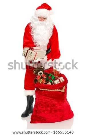 Santa Claus or Father Christmas handing you a gift from his sack full of toys, isolated on a white background. - stock photo