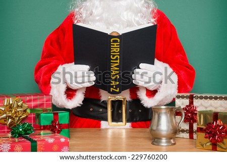 Santa Claus or Father Christmas reading a Christmas A-Z book whilst standing at his desk in the North Pole. - stock photo