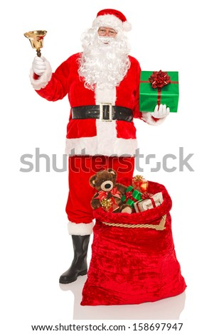 Santa Claus or Father Christmas with a sack full of gifts and holding a bell and green present, isolated on a white background.
