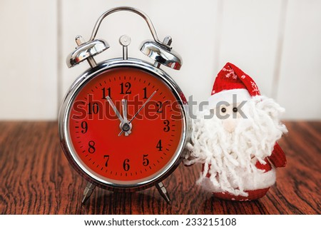 Santa Claus or Father Frost and vintage alarm clock with red dial on wooden background. Showing time five minutes before twelve midnight - stock photo