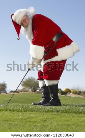 Santa Claus playing golf in leisure time - stock photo