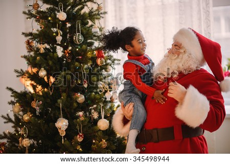 Santa Claus playing with cute african american Child at Home - stock photo