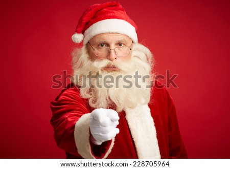 Santa Claus pointing and looking at camera in isolation - stock photo