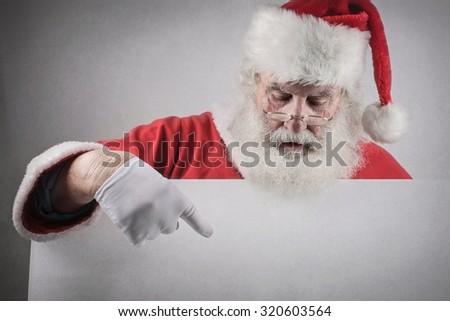 Santa Claus pointing at something - stock photo
