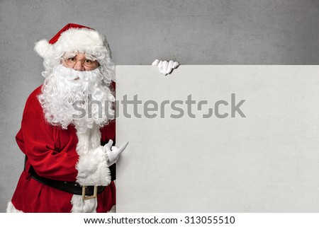 Santa Claus pointing in blank sign - stock photo