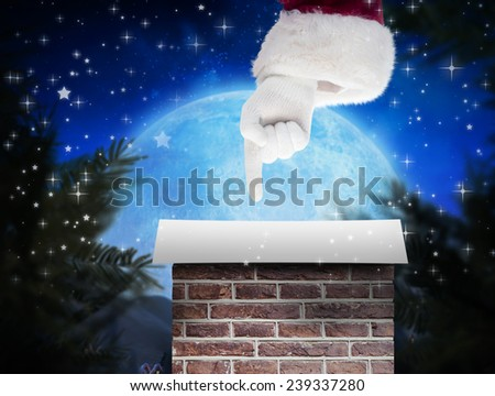Santa Claus points at something against twinkling stars - stock photo