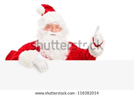 Santa Claus posing behind a blank billboard and giving a thumb up isolated on white background
