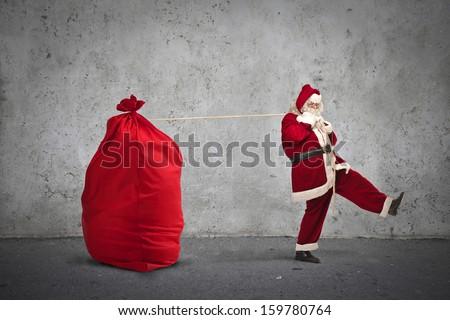 Santa Claus pulling big sack of Christmas - stock photo