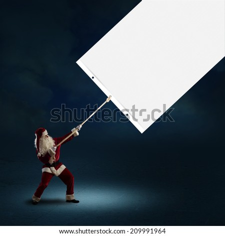 Santa Claus pulls a banner of cloth with a rope, place for text - stock photo