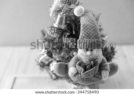 Santa Claus puppet on Christmas tree, Santa Claus against a Christmas tree:black & white - stock photo